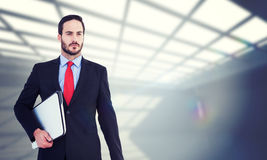 Composite image of handsome businessman holding briefcase and laptop Royalty Free Stock Images