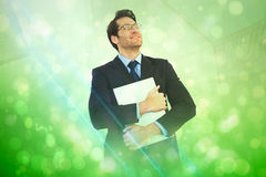 Composite image of handsome businessman holding his laptop Stock Photography