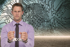 Composite image of handsome businessman wearing handcuffs Royalty Free Stock Image