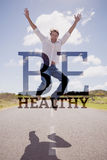 Composite image of handsome casual man leaping on a road smiling at camera Royalty Free Stock Photo