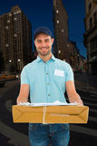 Composite image of handsome courier man with parcel Royalty Free Stock Photo