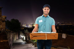 Composite image of handsome courier man with parcel Stock Photos