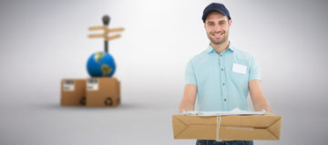 Composite image of handsome courier man with parcel. Handsome courier man with parcel against grey background Stock Photography