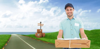 Composite image of handsome courier man with parcel. Handsome courier man with parcel against road leading out to the horizon Stock Photography