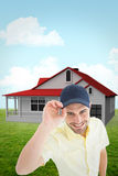 Composite image of handsome delivery man wearing baseball cap. Handsome delivery man wearing baseball cap against blue sky Royalty Free Stock Photography