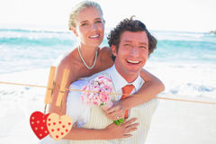 Composite image of handsome groom giving his new wife a piggy back. Handsome groom giving his new wife a piggy back against hearts hanging on the line Royalty Free Stock Photo