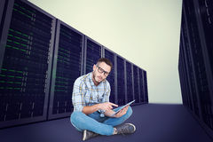Composite image of handsome hipster using tablet pc Royalty Free Stock Images