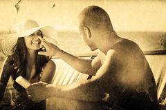 Composite image of handsome man applying sun cream on his girlfriends nose Stock Photo