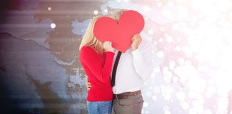 Composite image of handsome man getting a heart card form wife. Handsome men getting a heart card form wife against blurred white light Royalty Free Stock Image