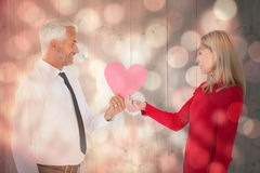 Composite image of handsome man getting a heart card form wife Royalty Free Stock Image