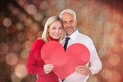 Composite image of handsome man getting a heart card form wife Stock Photo