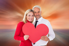 Composite image of handsome man getting a heart card form wife Stock Images