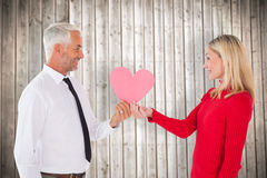 Composite image of handsome man getting a heart card form wife Royalty Free Stock Images