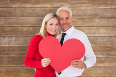 Composite image of handsome man getting a heart card form wife Royalty Free Stock Photos