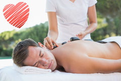 Composite image of handsome man getting a hot stone massage poolside Stock Image