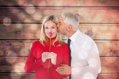 Composite image of handsome man giving his wife a kiss on cheek Stock Images
