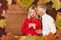 Composite image of handsome man giving his wife a kiss on cheek Stock Image