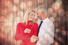 Composite image of handsome man giving his wife a pink rose Royalty Free Stock Images
