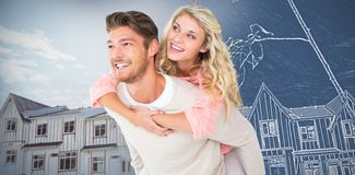 Composite image of handsome man giving piggy back to his girlfriend royalty free stock image