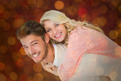 Composite image of handsome man giving piggy back to his girlfriend Royalty Free Stock Images