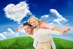Composite image of handsome man giving piggy back to his girlfriend Stock Photography