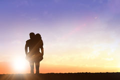 Composite image of handsome man giving piggy back to his girlfriend. Handsome men giving piggy back to his girlfriend against clouds stock photography