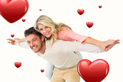 Composite image of handsome man giving piggy back to his girlfriend Royalty Free Stock Photos