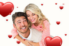 Composite image of handsome man giving piggy back to his girlfriend. Handsome men giving piggy back to his girlfriend against hearts Royalty Free Stock Photography