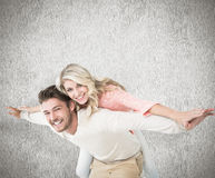 Composite image of handsome man giving piggy back to his girlfriend Stock Images