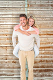 Composite image of handsome man giving piggy back to his girlfriend Stock Image