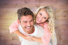 Composite image of handsome man giving piggy back to his girlfriend Stock Photos