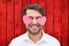 Composite image of handsome man with hearts over his eyes Stock Photos