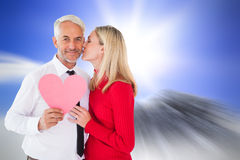 Composite image of handsome man holding paper heart getting a kiss from wife Royalty Free Stock Photography