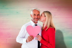 Composite image of handsome man holding paper heart getting a kiss from wife Royalty Free Stock Image