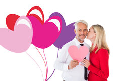 Composite image of handsome man holding paper heart getting a kiss from wife Stock Photos