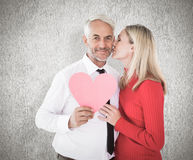 Composite image of handsome man holding paper heart getting a kiss from wife Royalty Free Stock Photo