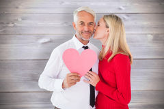 Composite image of handsome man holding paper heart getting a kiss from wife Stock Image