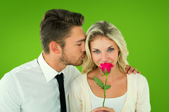 Composite image of handsome man kissing girlfriend on cheek holding a rose Stock Photo