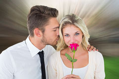Composite image of handsome man kissing girlfriend on cheek holding a rose Stock Image