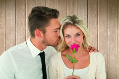 Composite image of handsome man kissing girlfriend on cheek holding a rose Royalty Free Stock Photos