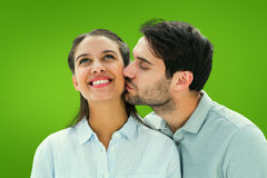 Composite image of handsome man kissing girlfriend on cheek Royalty Free Stock Image