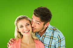 Composite image of handsome man kissing girlfriend on cheek Stock Image