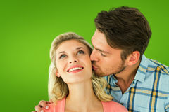 Composite image of handsome man kissing girlfriend on cheek Stock Photos