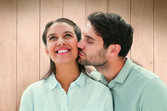 Composite image of handsome man kissing girlfriend on cheek Royalty Free Stock Photo
