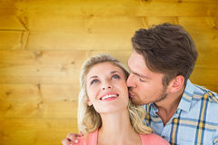 Composite image of handsome man kissing girlfriend on cheek Stock Photo