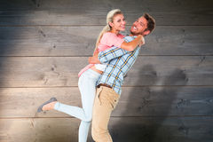 Composite image of handsome man picking up and hugging his girlfriend. Handsome men picking up and hugging his girlfriend against bleached wooden planks stock image