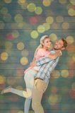 Composite image of handsome man picking up and hugging his girlfriend Royalty Free Stock Photography