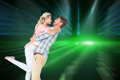 Composite image of handsome man picking up and hugging his girlfriend Stock Images