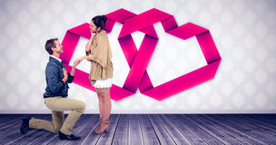 Composite image of handsome man proposing woman while kneeling. Handsome men proposing women while kneeling against room with wooden floor Royalty Free Stock Images