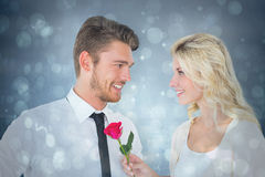 Composite image of handsome man smiling at girlfriend holding a rose. Handsome men smiling at girlfriend holding a rose against blue abstract light spot design Stock Photography